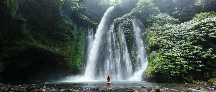 girl standing under bali waterfall