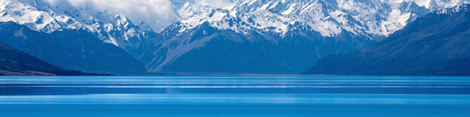 Image of blue bay water in foreground with snow-capped mountains and clouds in the distance